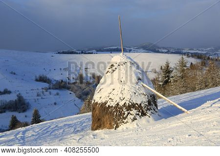 traditional carpathian haystack on mountain slope in winter time, Ukraine