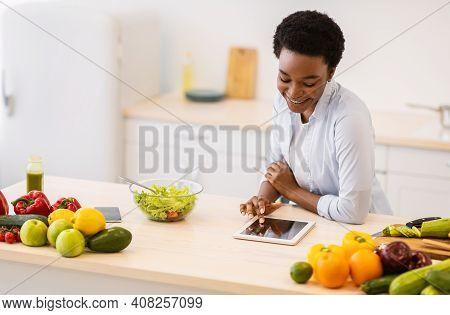 Black Woman Using Digital Tablet Cooking Browsing Healthy Recipes Online Preparing Dinner In Modern