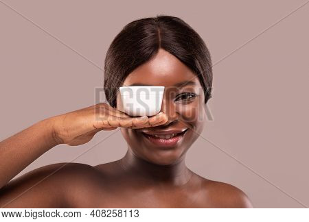 Portrait Of Beautiful Black Woman Covering One Eye With White Jar Of Moisturising Cream, African Lad