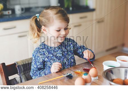 Excited Little Toddler Girl Coloring Eggs For Easter. Cute Happy Child Looking Surprised At Colorful