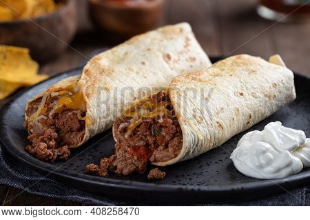 Closeup Of Two Beef Burritos And Sour Cream On A Black Plate