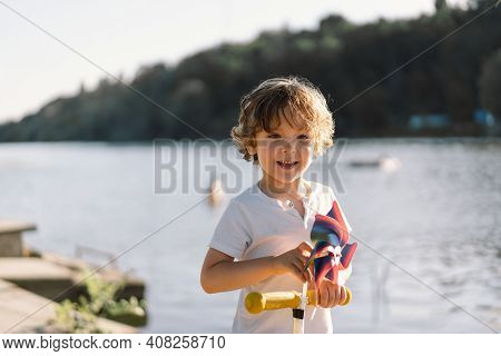 Portrait Of A Boy Playing In Nature Near The River.