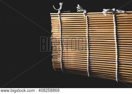 Thin Bamboo Sticks Are Tied With A Rope. Wooden Mat For Making Sushi And Rolls. Japanese Cuisine Che