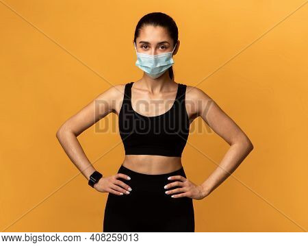 Sport And Quarantine Concept. Portrait Of Athletic Fit Woman Wearing Surgical Medical Face Mask Posi