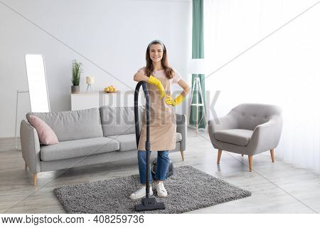 Housecleaning Service. Happy Young Maid With Vacuum Cleaner Standing In Middle Of Tidy Living Room,