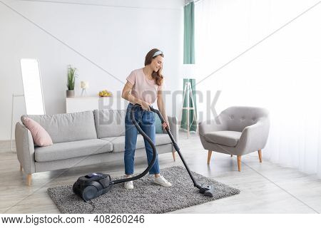 Cheerful Female Housekeeper Using Vacuum Cleaner To Tidy Apartment, Full Length Portrait. Positive Y