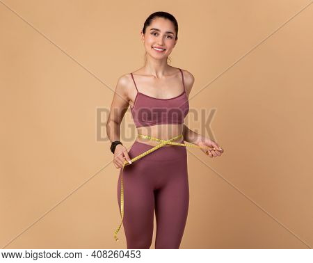 Weight Loss And Healthy Lifestyle Concept. Smiling Slim Woman Measuring Her Waist With Yellow Tape O