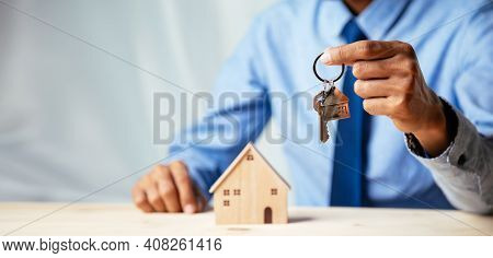 House Model With Real Estate Agent And Customer Discussing For Contract To Buy House, Insurance Or L