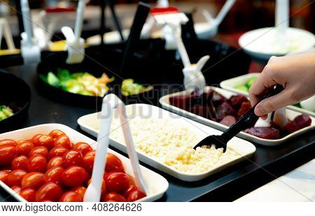 Hand Holding Spoon To Scoop Boiled Job's Tears At Salad Bar. Salad Bar Buffet At The Restaurant. Sal