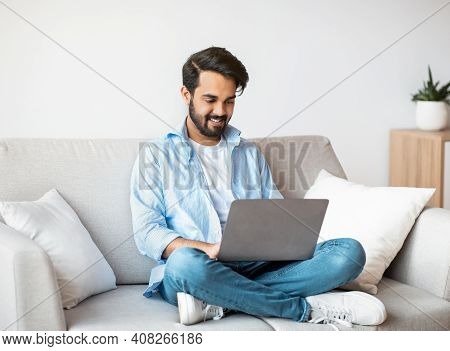 Distant Work. Happy Arab Freelancer Man Using Laptop Computer At Home, Typing On Keyboard, Young Eas