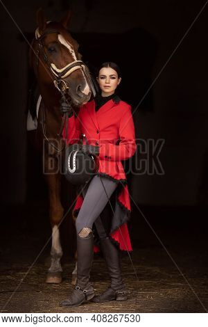 Rider Jockey Woman In Red Frock Coat Holds Horse By Bridle, Fashion Photo Black Background
