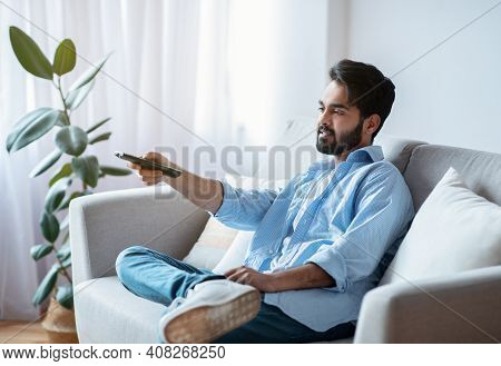 Arab Man With Remote Controller Switching Channels While Watching Tv At Home, Young Eastern Guy Rela