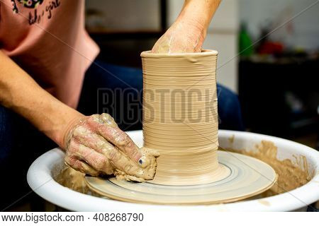 The Woman Potters Hands Formed By A Clay Pot On A Potters Wheel. The Potter Works In A Workshop