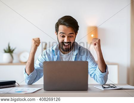 Excited Arab Guy Celebrating Success With Laptop Computer At Home Office, Emotionally Reacting To Go