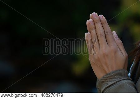 Praying Hands With Faith In Religion And Belief In God On Dark Background. Pay Respect.  Namaste Or