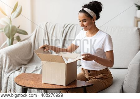 Happy Young Woman Unpacking Delivery Box, Sitting On Couch By Tea Table, Home Interior. Satisfied Cu
