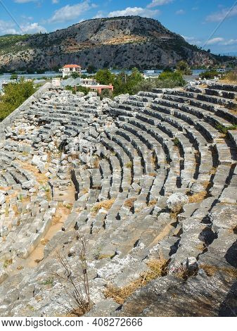 Rows of stone seats of ruins of Theatre in Letoon Ancient City in village Kumluova, Turkey. Sunny day, Greek culture ancient amphitheater architecture vertical photo