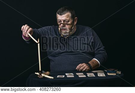 Nice Low Key Portrait Of Senior Man In Mask - Soothsayer  Lighting Candle While Doing Cartomancy