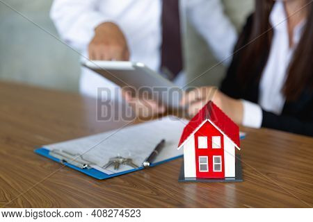 Red Roof House Placed On The Table In Agent's Hand Signed A Contract, Signature On An Official Docum