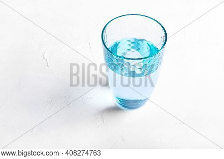 Blue Glass Of Purified Water On White