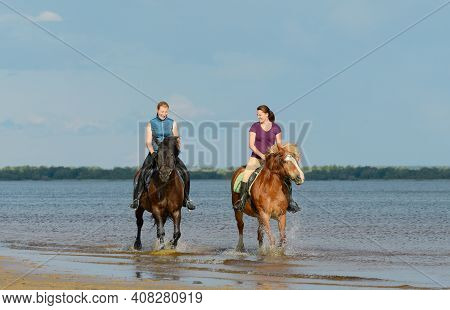 Two Woman Are Riding On Horseback On Water. Two Laughing Female Rider Are Riding Astride In Outdoors