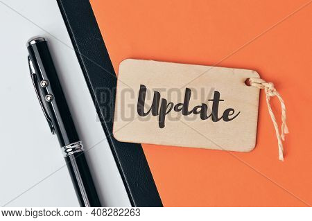 Top View Of Pen, Paper Holding File And Wooden Board Written With Update