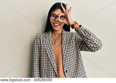 Young chinese woman wearing business style and glasses doing ok gesture with hand smiling, eye looking through fingers with happy face.