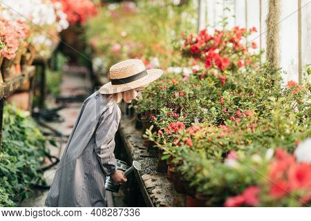 Child Planting Spring Flowers. Little Girl Gardener Plants Azalea. Girl Holding Azalea Bush In Flowe