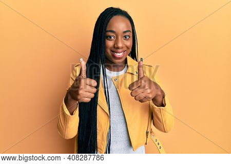 Young african american woman wearing casual jacket success sign doing positive gesture with hand, thumbs up smiling and happy. cheerful expression and winner gesture.