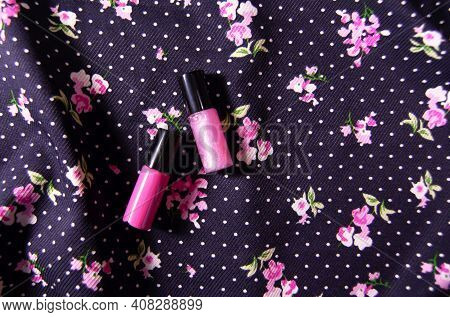 Pink Lipstick And Pink Glitter Lip Gloss On Floral Fabric Backdrop