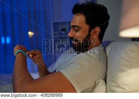 people, bedtime and rest concept - happy smiling indian man looking at health tracker in bed at home at night