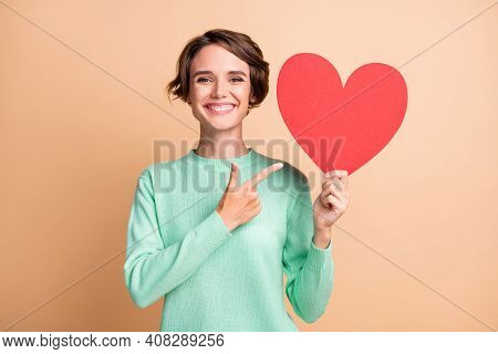 Photo Of Young Attractive Positive Woman Smile Point Finger Paper Heart Advert Promo Recommend Isola