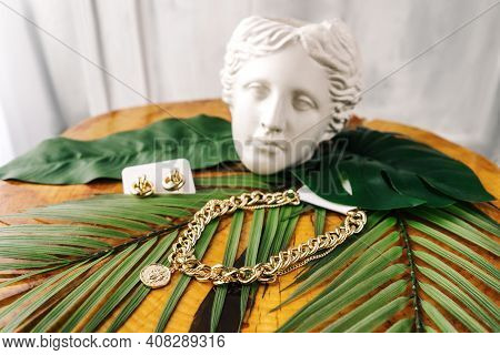 Imitation Jewelry, Golden Bijouterie Chain And Earrings On Leaves On Wooden Table. White Gypsum Fema