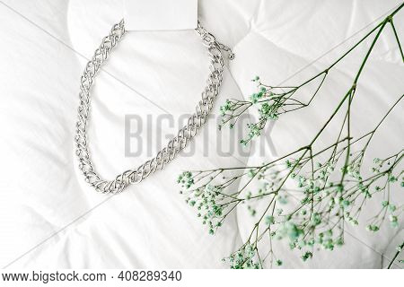Imitation Jewelry, Silver Bijouterie Chain On White Textile Background. Blue Dry Little Flowers Like