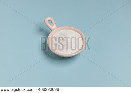 Collagen Powder Or Protein In Pink Bowl On Blue Background. Cosmetic Skin Care Concept.