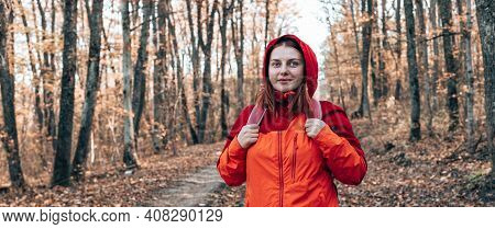 A Young Beautiful Smiling Girl In Bright Sports Clothes With A Backpack Travel Looks Into The Camera
