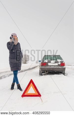 Young Woman Stands Near The Triangle Road Warning Sign And Talks On Her Mobile Phone Against The Bac