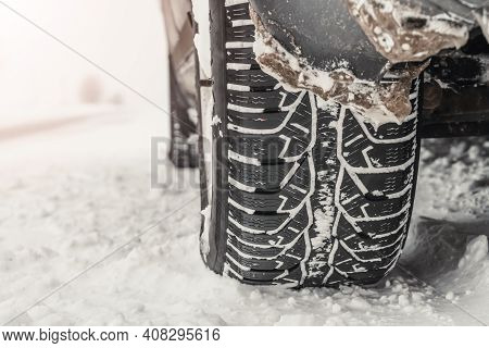 Close-up Of The Rear Wheel Of A Car In The Snow. Winter Tire In The Snow. Copy Space