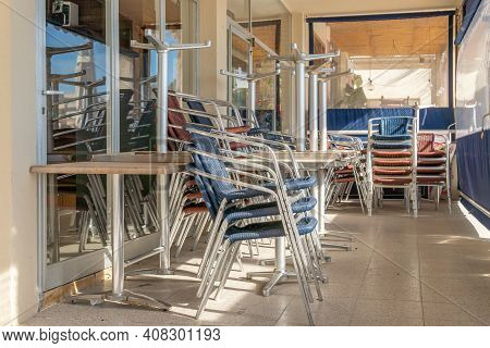 Metal Chairs And Tables Stacked Outdoor. Restaurant Businesses Closed By Coronavirus Crisis