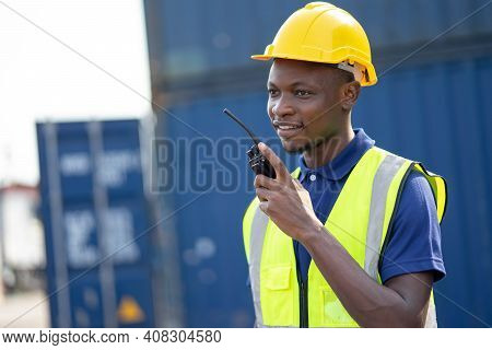 American African Engineer Or Factory Worker Man Working  At Container Cargo Harbor To Loading Contai