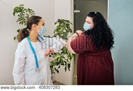 Overweight Woman And Her Doctor Wearing Medical Masks Greeting Each Other By Elbow Bumping At Doctor