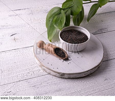 Black Raw Quinoa Seeds In White Bowl And Wooden Scoop With Seeds On White Wooden Table. Few Seeds Ar