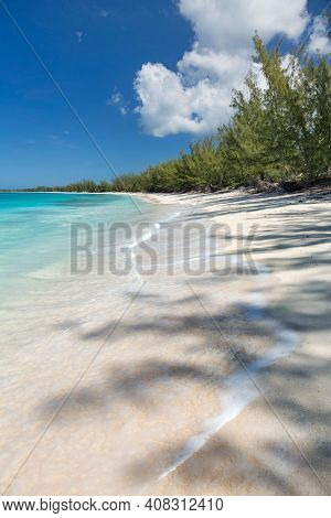 Turquoise water and waves along the shoreline at Man O' War Beach on Cat Island, Bahamas.