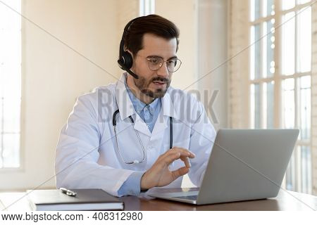 Concentrated Skilled Male General Practitioner Consulting Patient Online.
