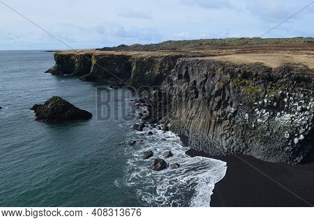 Waves On The Black Sand Beach With Basalt Columns.