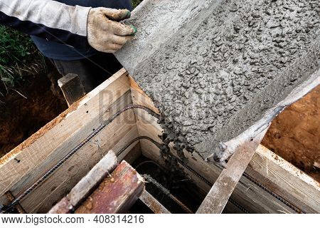 The Concrete Mixer Loads The Concrete Through A Chute Into A Timber Formwork With Metal Reinforcemen
