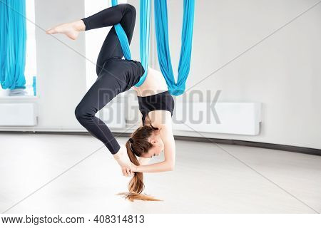 Young Woman Performing Antigravity Aerial Yoga Exercise In White Studio. Concept Meditation