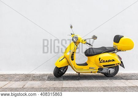 October.10.2019: Santorini, Greece - Vintage Yellow Vespa Parking At The Wooden Wall Of The Restaura