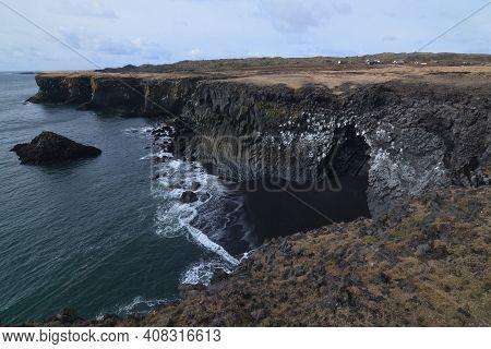 Lovely Rock Cliffs And Basalt Column Rocks And Sand Beach.