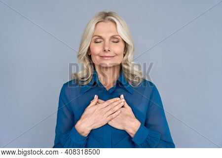 Happy Mindful Thankful Middle Aged Old Woman Holding Hands On Chest Meditating With Eyes Closed Isol